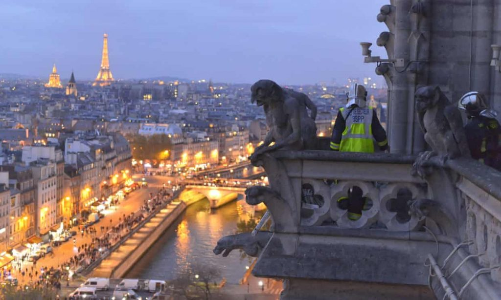 A Pompier Or French Fireman High On Notre Dame