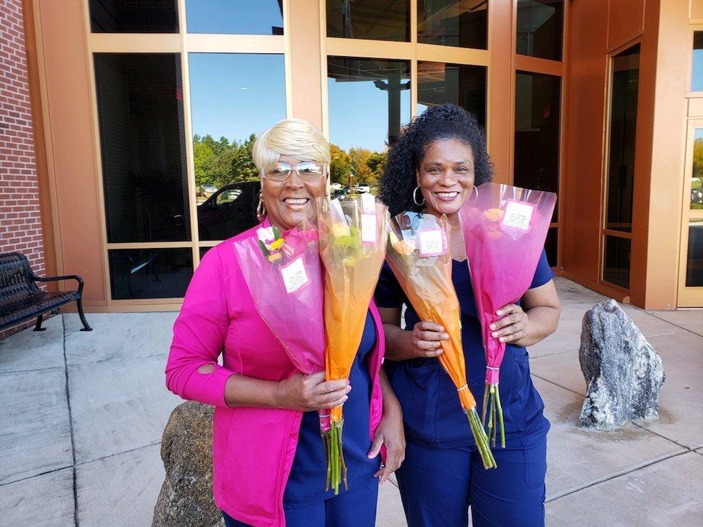 Two women receive free flower bouquets